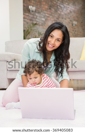 Happy mother with her baby using laptop on the carpet in living room - stock photo