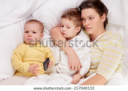happy mother with her child on white bed, shot from above, little girl crying - stock photo