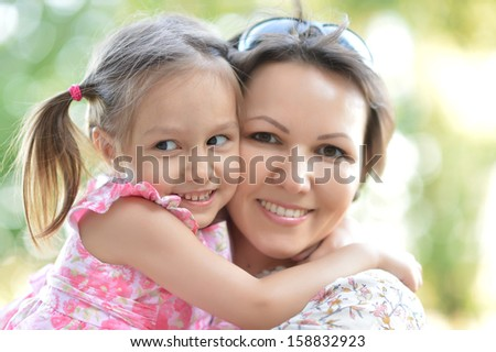 happy mother with her cute daughter on the walk - stock photo