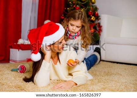 happy mother with her daughter playing near the Christmas tree - stock photo
