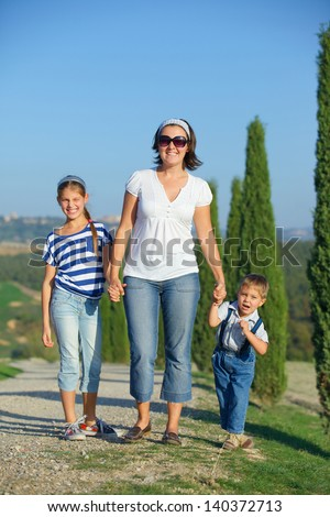 Happy mother with her kids having fun on vacations in Tuscan against cypress alley background - stock photo