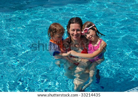 Happy mother with her kids in swimming pool - stock photo