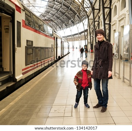 Happy mother with her son on train station platform - stock photo