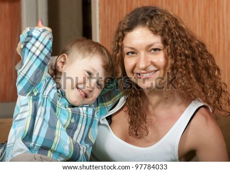 Happy mother with her son  sitting on sofa - stock photo