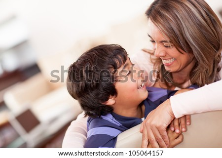 Happy mother with her son smiling at home - stock photo