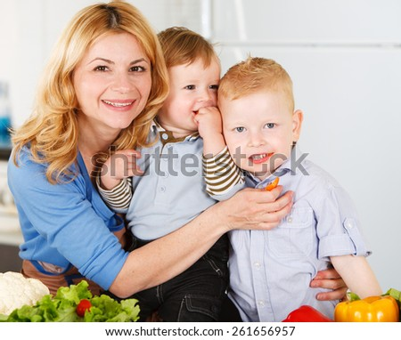 Happy mother with her sons having fun in the kitchen - stock photo