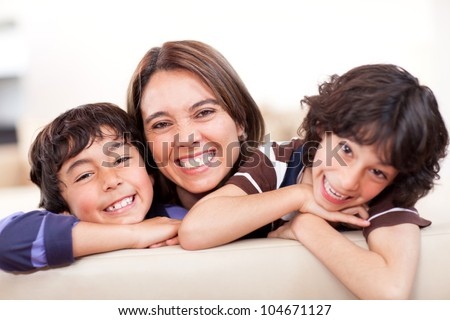 Happy mother with her two sons smiling at home - stock photo