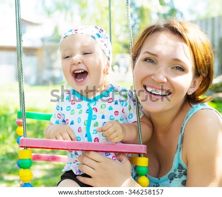 Happy mother with laughing baby sits on the swing  - nature portrait - stock photo