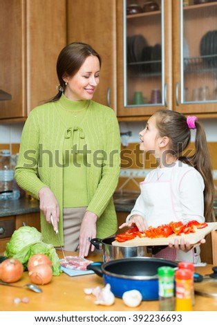 Happy mother with little cheerful daughter cooking at home kitchen and smiling - stock photo
