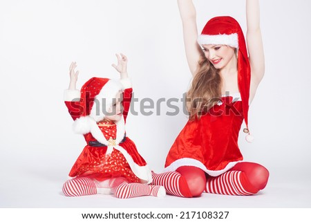 Happy mother with little daughter iin the Santa Claus clothes - stock photo
