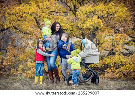 Happy mother with small children walking in autumn - stock photo