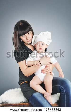happy mother with the baby in a suit of the cook - stock photo