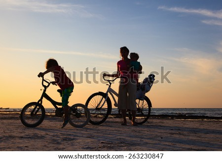 happy mother with two kids biking at sunset - stock photo