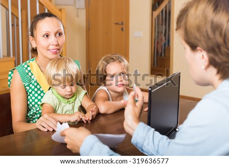 Happy mother with two little children glad hearing words of social worker at home - stock photo