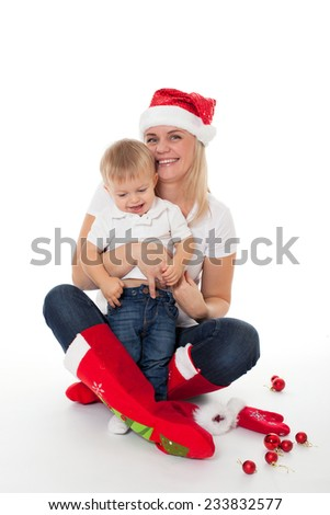 Happy mother woman girl in santa hat and christmas socks with little baby boy son kid isolated on white  - stock photo