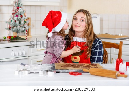 Happy mother, young woman in red santa hat baking christmas cookies together with her little daughter, cute blonde kid girl, sitting at the table in domesti? kitchen. Kid giving mum a kiss. - stock photo