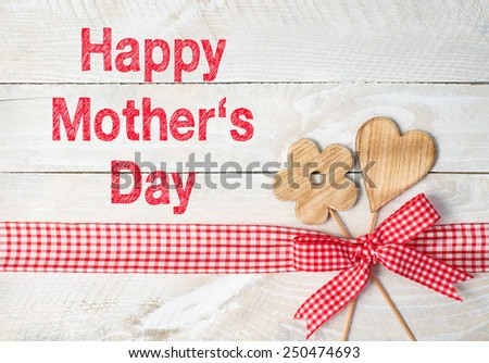 Happy Mothers Day - flower and heart with red ribbon on wooden background - stock photo