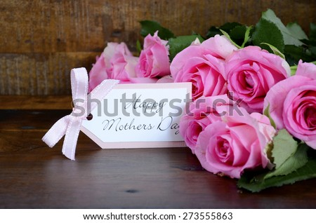 Happy Mothers Day fresh pink roses on dark wood distressed table and background, with gift tag.   - stock photo