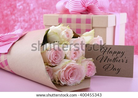 Happy Mothers Day gifts of pink roses and gift box wrapped in brown kraft paper on pink wood table, and greeting gift tag card.  - stock photo