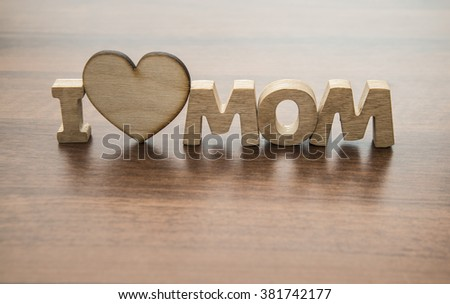 Happy Mothers day. I Love my mom Concept. Wood heart and Wooden letters spelling. Image with shadows on table. - stock photo