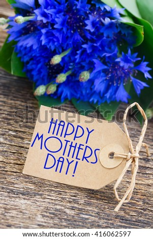 happy mothers day  paper tag with Blue fresh cornflowers on wooden table with copy space - stock photo