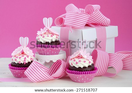 Happy Mothers Day pink and white cupcakes on retro style cake stands and large gift box on vintage white wood table. - stock photo