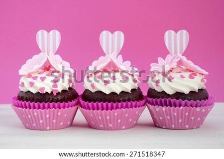 Happy Mothers Day pink and white cupcakes with heart shape topper and hearts and flowers decorations on vintage white wood table. - stock photo