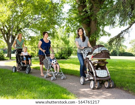 Happy mothers with their baby strollers walking together in park - stock photo