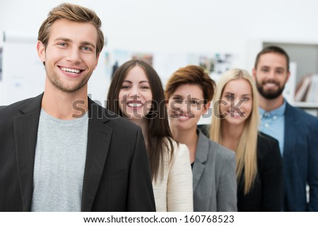 Happy motivated business team of diverse young professional men and women standing in a receding row headed by their handsome young team leader - stock photo