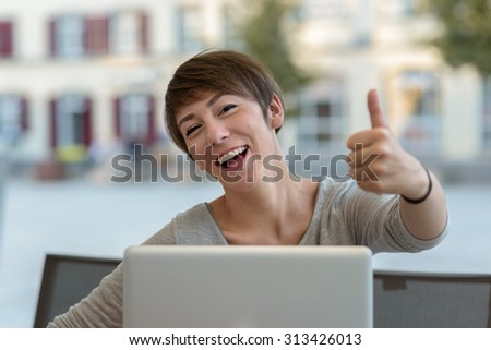 Happy motivated businesswoman giving a thumbs up gesture with a laughing smile as she sits working at her laptop computer at an open-air restaurant in an urban street - stock photo