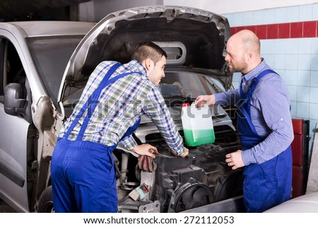 Happy mounting specialists in coveralls working at auto repair shop - stock photo