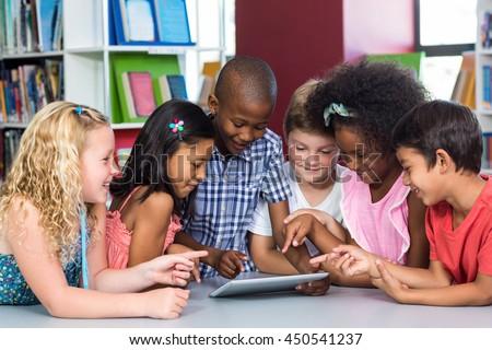 Happy multi ethnic children using digital table in library - stock photo