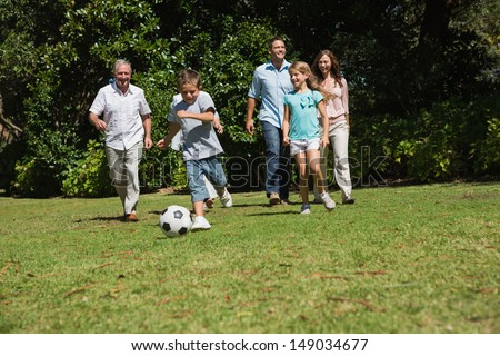 Happy multi generation family playing football together in the park - stock photo