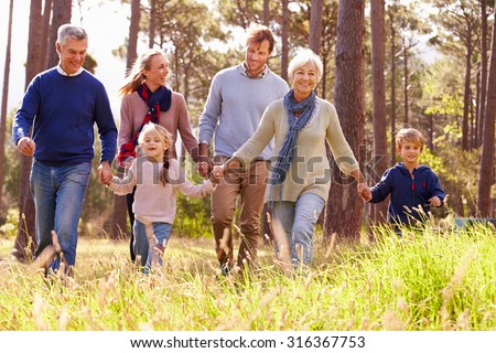 Happy multi-generation family walking in the countryside - stock photo