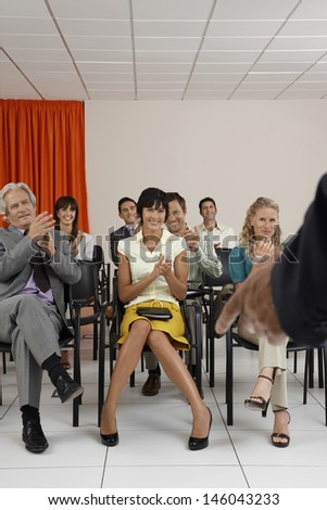 Happy multiethnic businesspeople applauding a speaker in conference room - stock photo