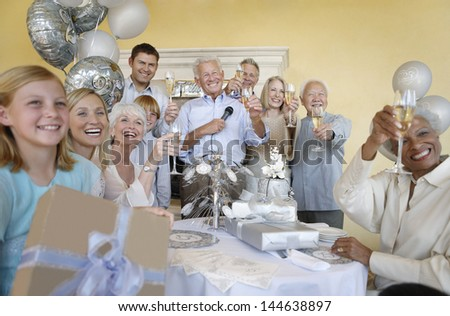 Happy multiethnic family and friends toasting champagne in a party - stock photo