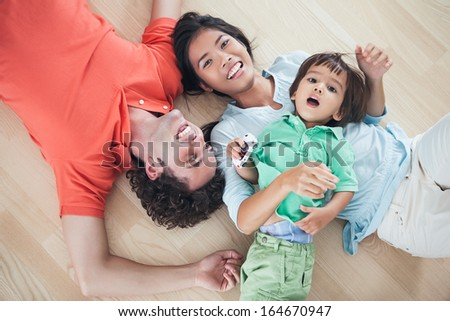 Happy multiethnic family lying on the floor together. - stock photo