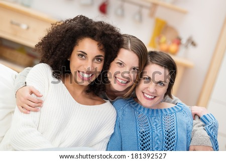Happy multiethnic group of beautiful young female friends sitting arm in arm on a sofa in the living room smiling at the camera - stock photo
