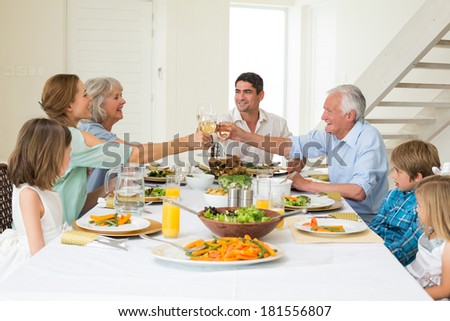 Happy multigeneration family toasting while having meal at dining table - stock photo
