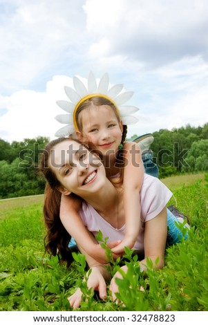 Happy mum and daughter in grass - stock photo