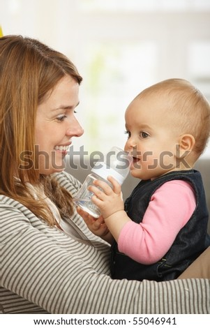 Happy mum holding baby girl in arms smiling. - stock photo