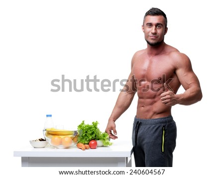 Happy muscular man standing with thumbs up near healthy food - stock photo