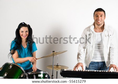 Happy musical band with man and woman playing drums and organ - stock photo