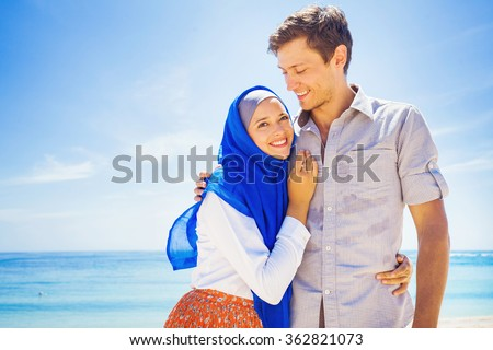 happy muslim couple on a beach - stock photo