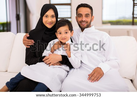 happy muslim family sitting on the couch at home - stock photo