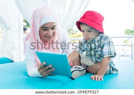 Happy Muslim young woman and little boy on summer vacation - stock photo