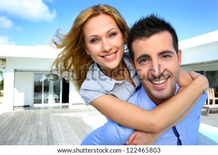 Happy new property owners in front of their house - stock photo