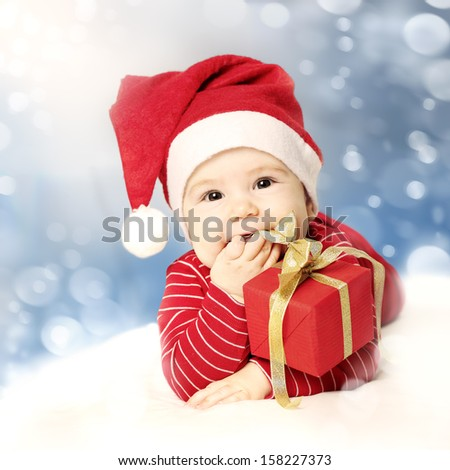 Happy New Year baby with red gift on snow background - stock photo