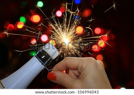 Happy new year background with woman hand opening champagne - stock photo