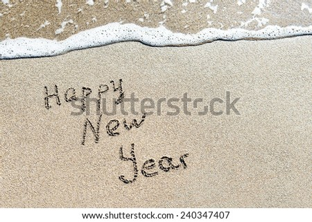 Happy New Year caption at wet beach sand with sea wave foam - stock photo